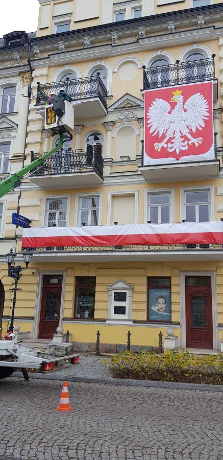 mężczyźni dekorują miejsca pamięci narodowej na Święto Niepodległości