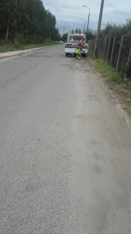 czyszczenie chodnika przez pracowników ZOM