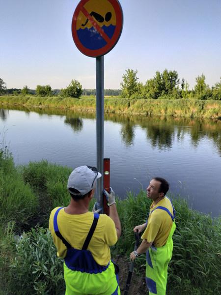 """pracownicy MPGKiM montują znak """"Zakaz pływania"""""""