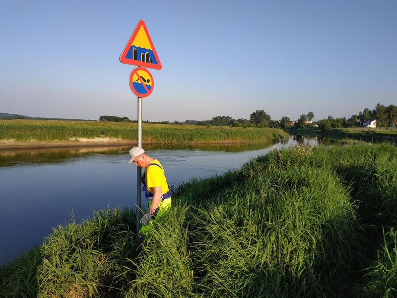 """pracownik MPGKiM montują znak """"Zakaz pływania"""""""