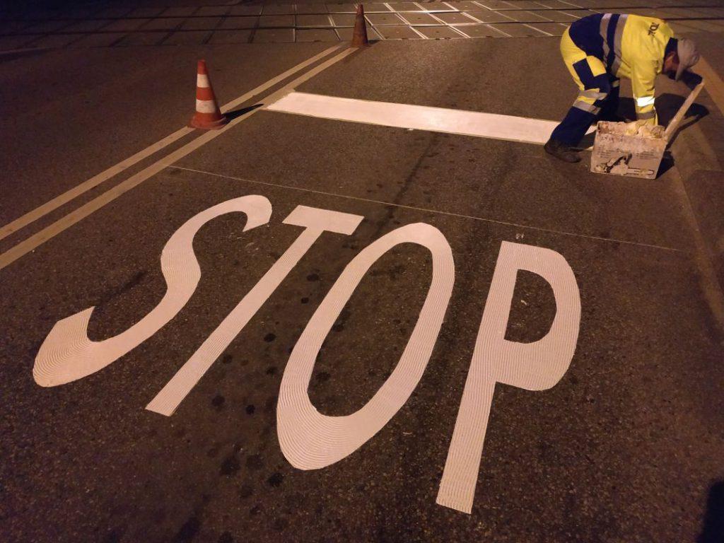 pracownik MPGKiM maluje białą linię przy przejeździe kolejowym nad znakiem STOP