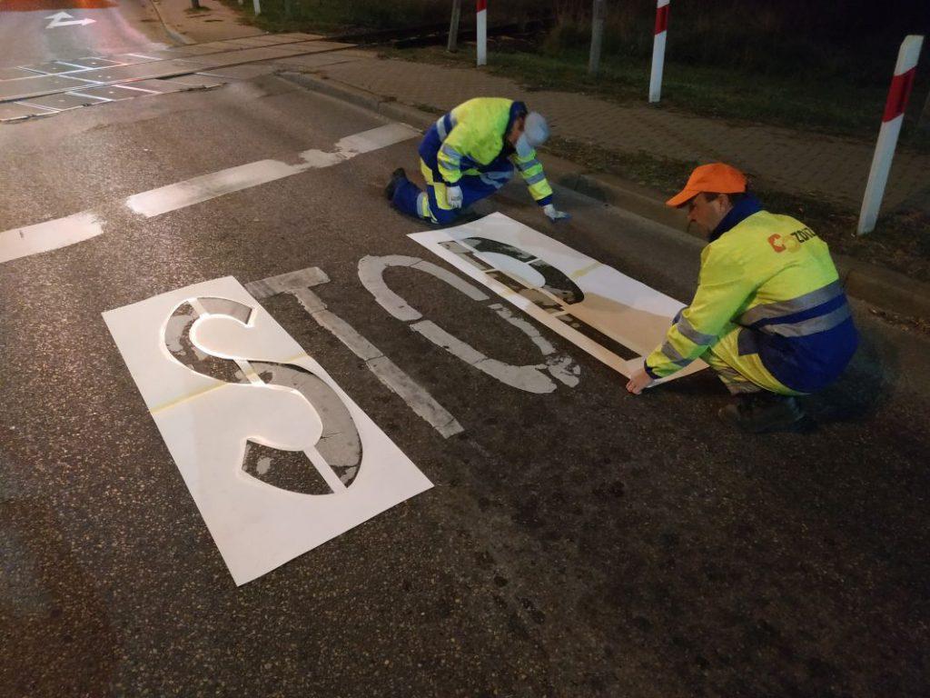 pracownicy MPGKiM malują znak STOP przy przejeździe kolejowym