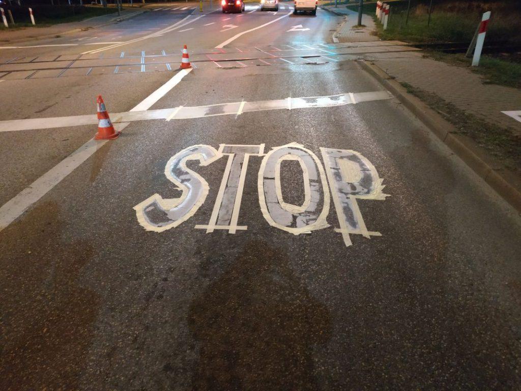 namalowany znak STOP przy przejeździe kolejowym podczas schnięcia