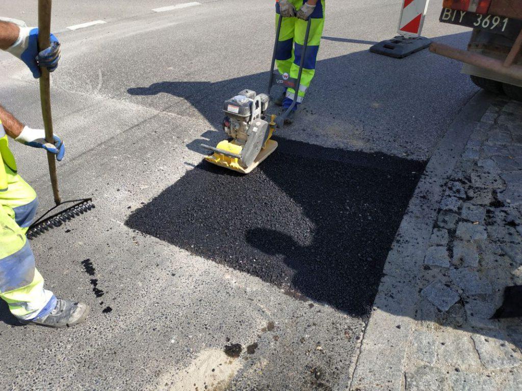 mężczyzna utwardza maszyną wylany asfalt