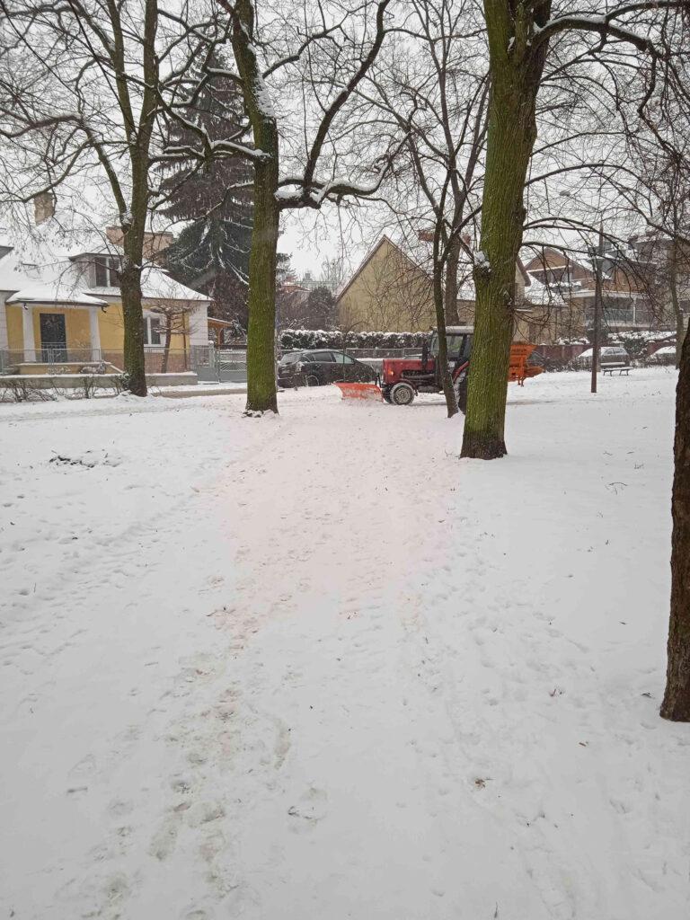 odśnieżanie traktorem ścieżek w parku