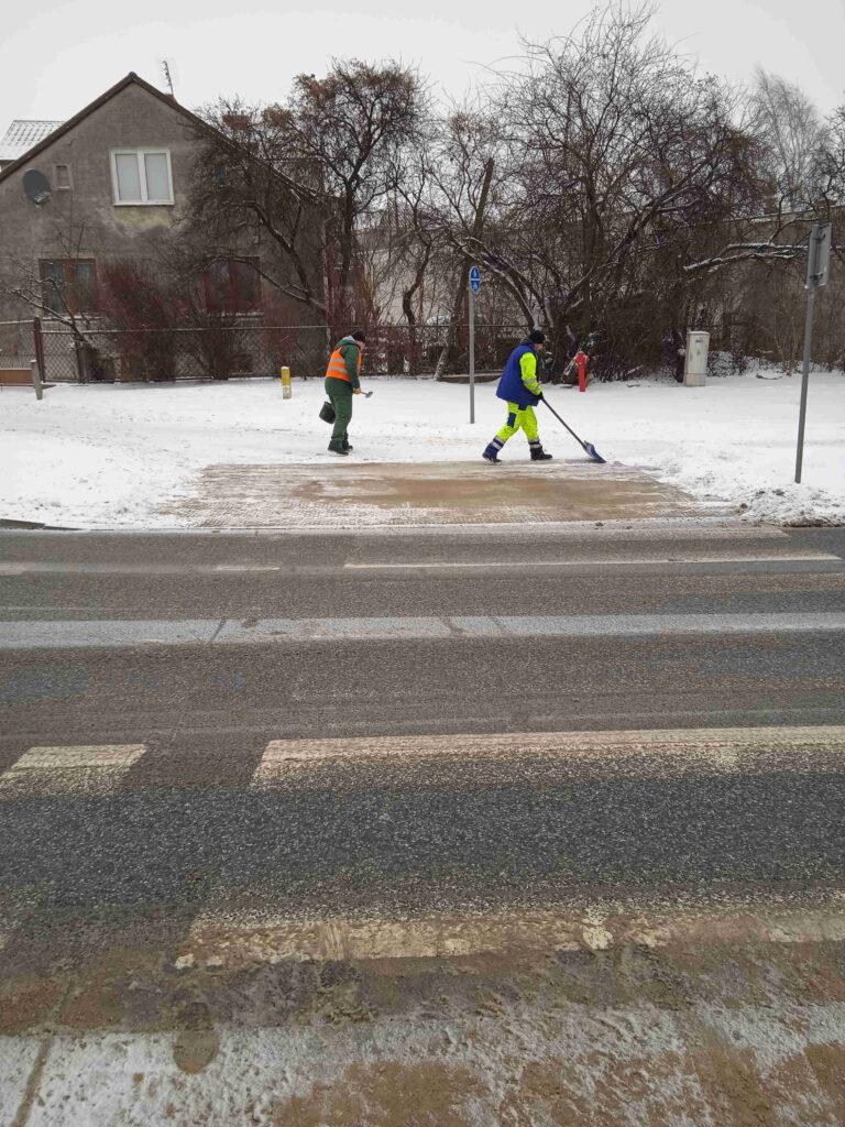 mężczyzni odśnieżają dojście do przejścia dla pieszych