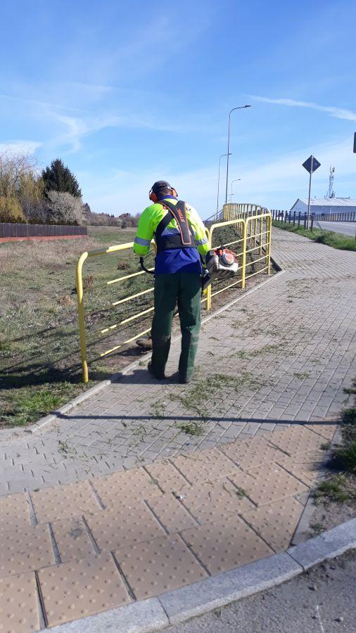mężczyzna kosi trawę przy żółtych barierkach ochronnych