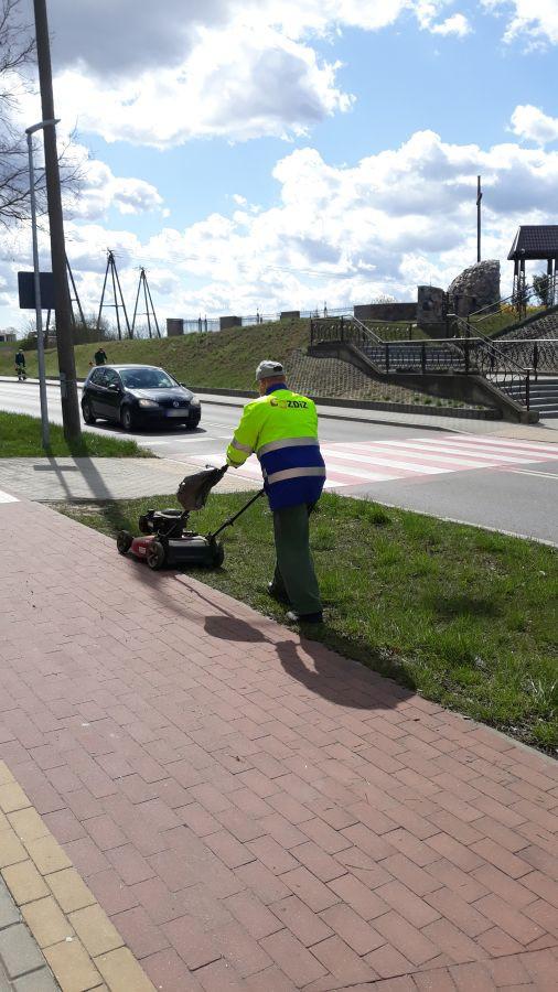 mężczyzna kosi trawę kosiarką spalinową przy chodniku i ulicy