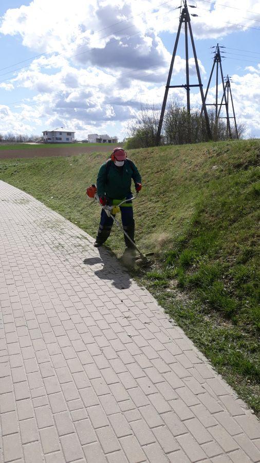 mężczyzna kosi trawę przy chodniku