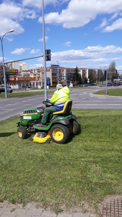 mężczyzna kosi trawę traktorkiem