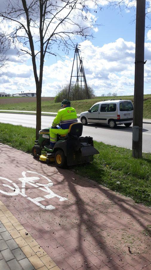 mężczyzna kosi trawę traktorkiem przy chodniku