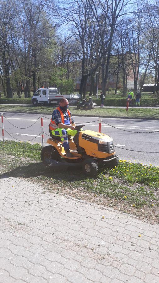 mężczyzna kosi trawę traktorkiem przy ulicy