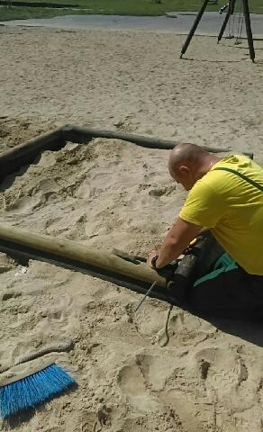pracownik MPGKiM naprawia piaskownicę