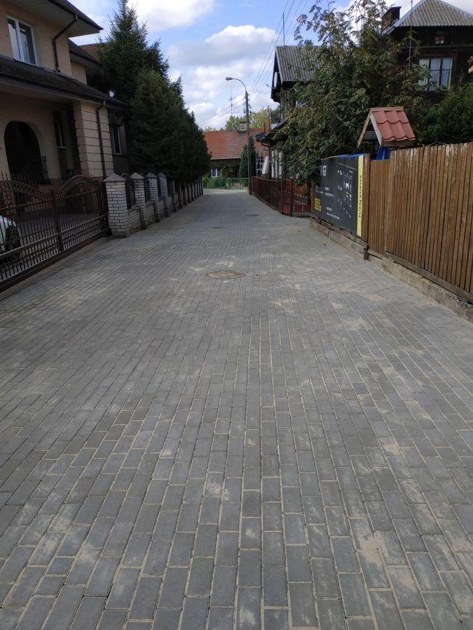 widok na nowo wyłożoną ulicę z kostki brukowej