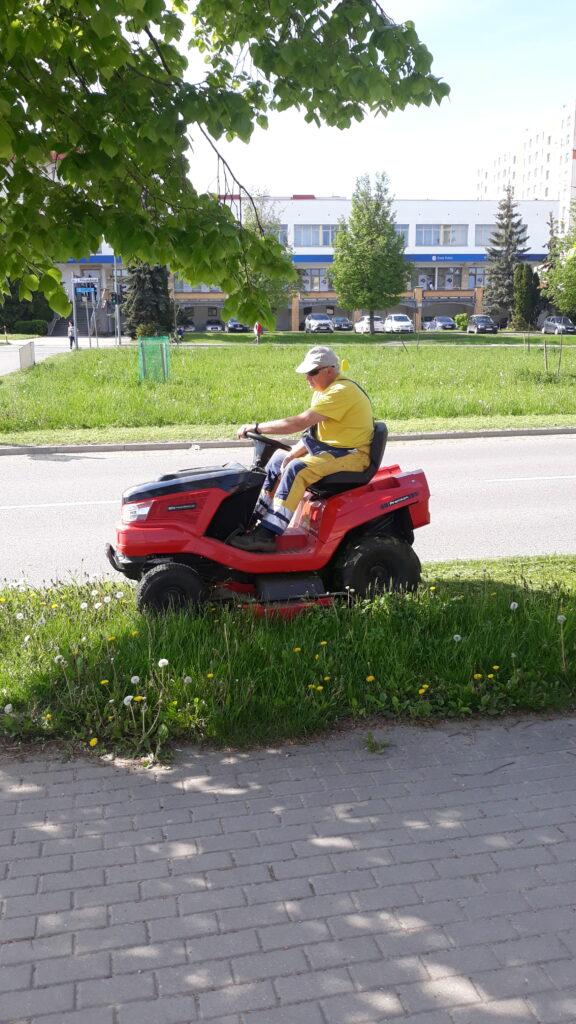 mężczyzna kosi trawę kosiarką samojezdną