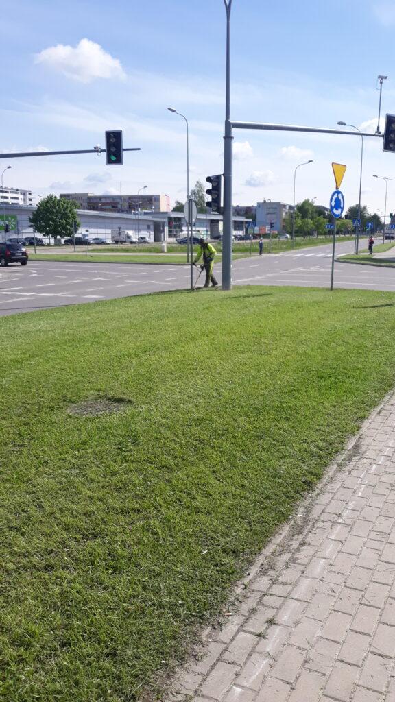 mężczyzna wykasza trawę wykaszarką