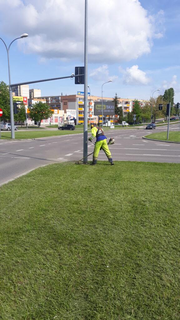 mężczyzna kosi trawę wykaszarką