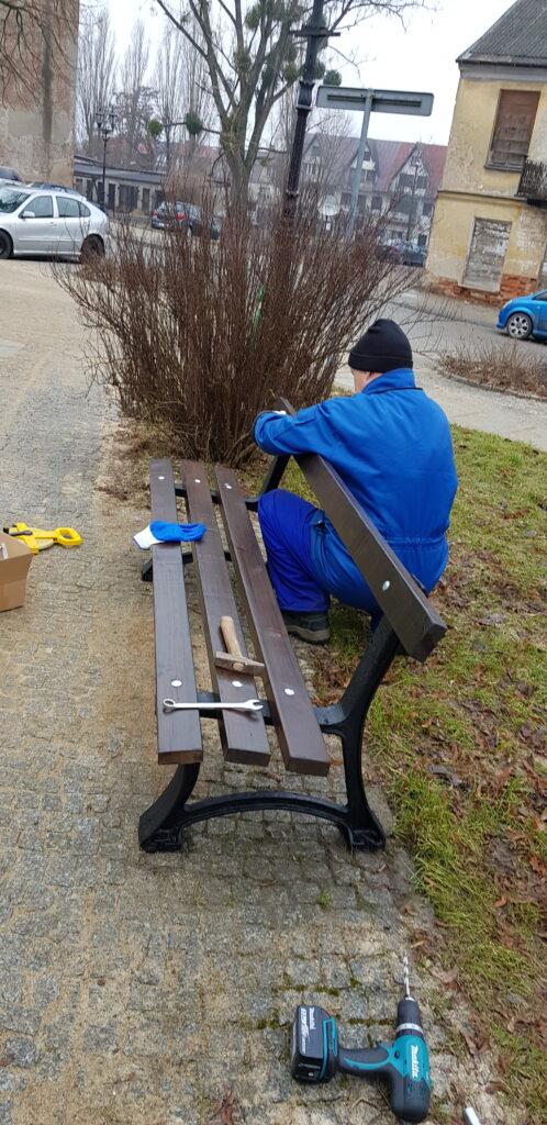 mężczyzna przeprowadza renowację ławki